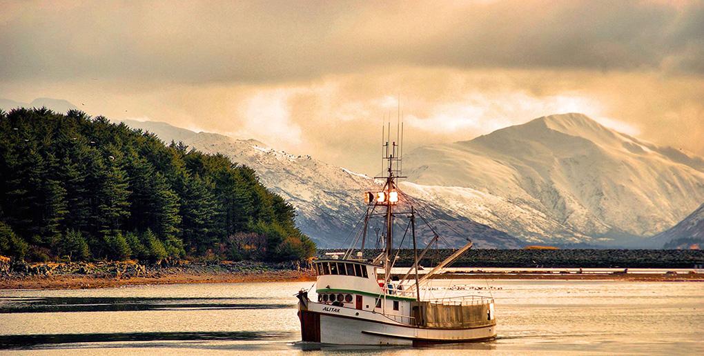 アラスカの春、漁船と雪山の夕景